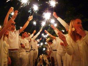 Diner En Blanc participants hold up sparklers.